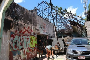 Two builders working  at the site of the restoration of the derelict Red Hill Skate Arena in Brisbane. PHOTO: Cleaning work has begun on the arena that has been neglected since being gutted by fire in 2002. (ABC News: Ashleigh Stevenson)