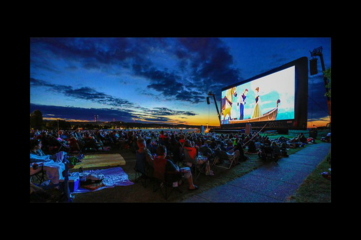 Outdoor cinema screen with crowd