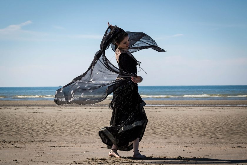 Woman in a sari dances on the beach. Photo by Shlag on Unsplash