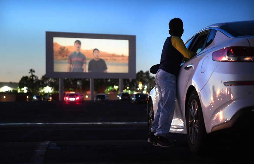 boy watches drive-in cinema screen