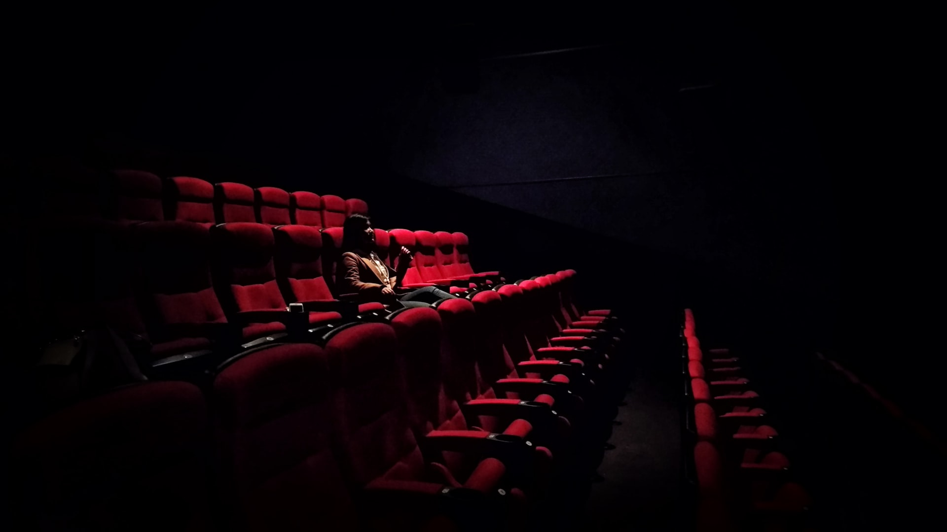 Woman alone in cinema. Photo by Karen Zhao/Unsplash
