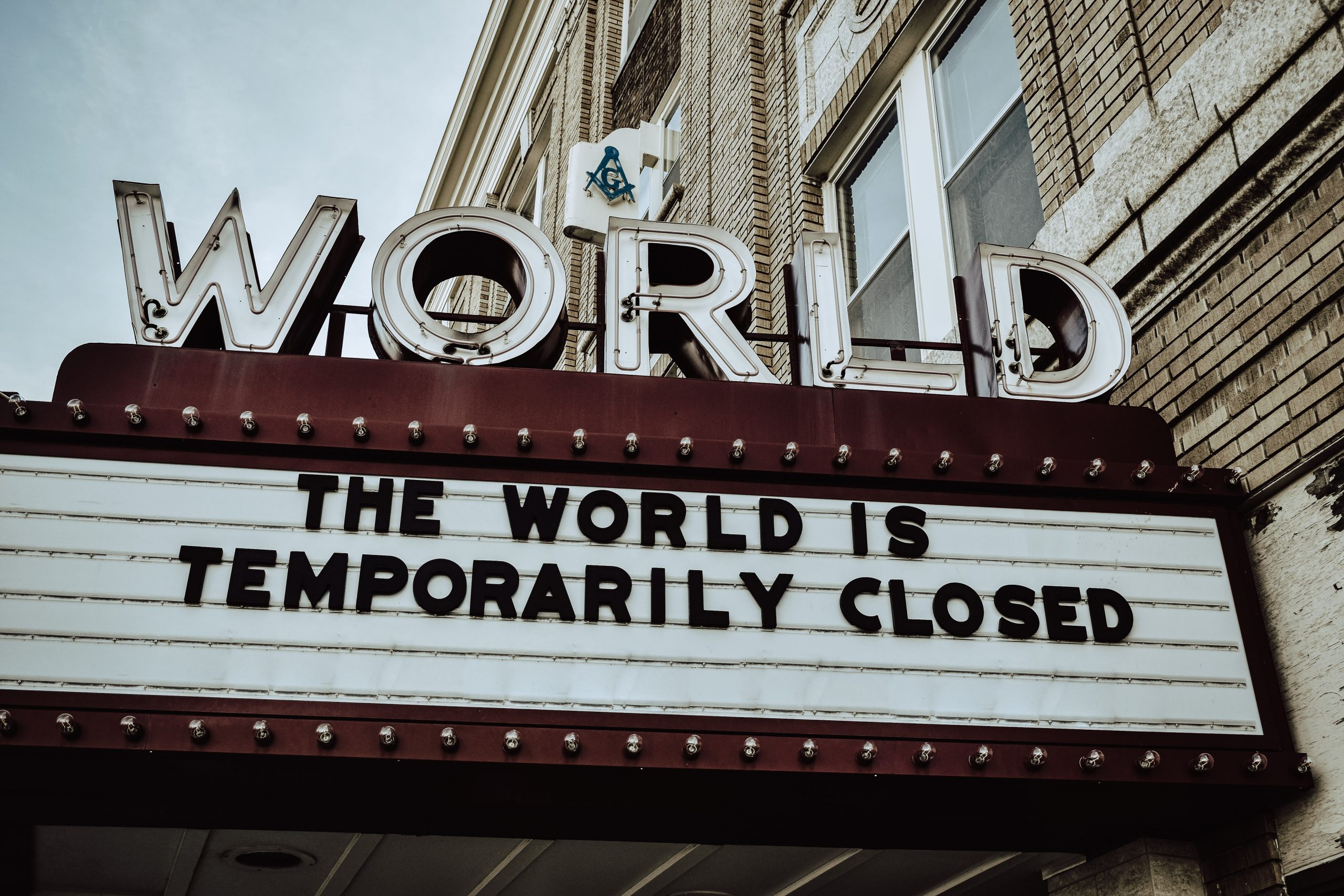 "billboard saying 'The World is temporarily closed"" photo by Edwin Hooper on Unsplash"