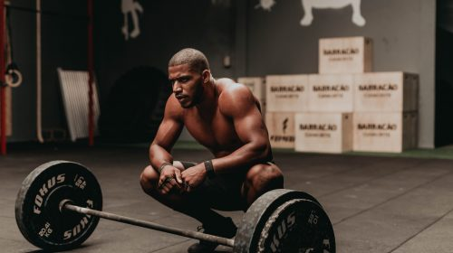 Man waits to lift weights. Photo by Allef Vinicius on Unsplash