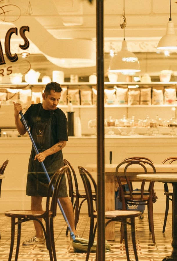 Man mopping cafe. Photo by Zhanjiang Chen on Unsplash cropped