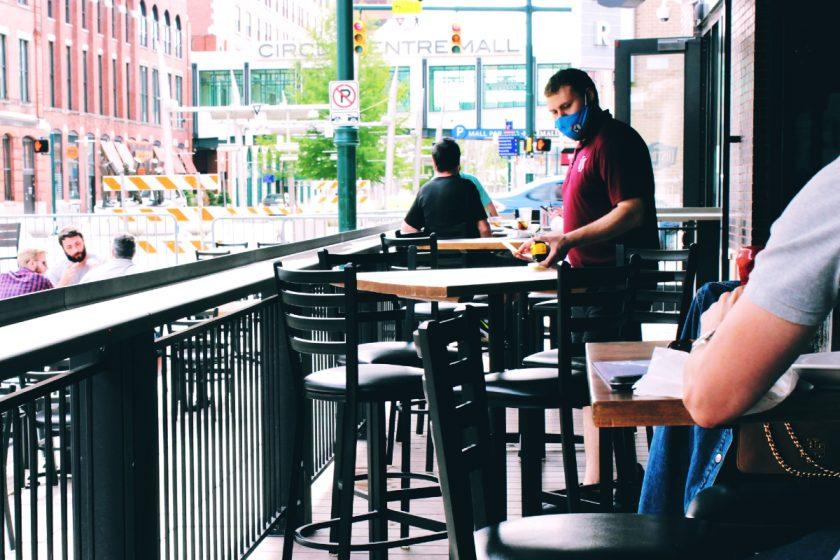 Restaurant near mall. Server in mask. Photo by Danielle Rice on Unsplash