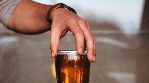 Hand holding pint of beer. Photo by Pawel Kadysz on Unsplash